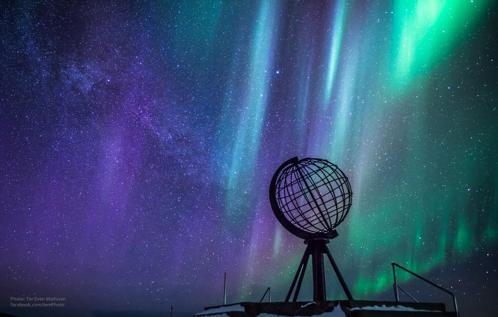Aurora Borealis sul promontorio di Capo Nord (Nordkapp) con il simbolo del mappamondo nella notte polare