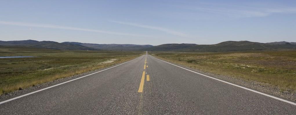 Strada norvegese senza fine verso l'infinito all'orizzonte